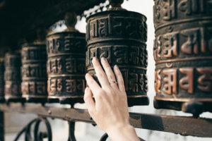 female hand touches the Buddhist prayer drum, Nepal